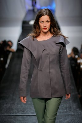 Model wearing grey top with green pants by Anna Arguello