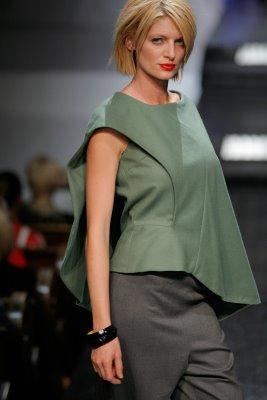 Model wearing green top with grey skirt by Anna Arguello
