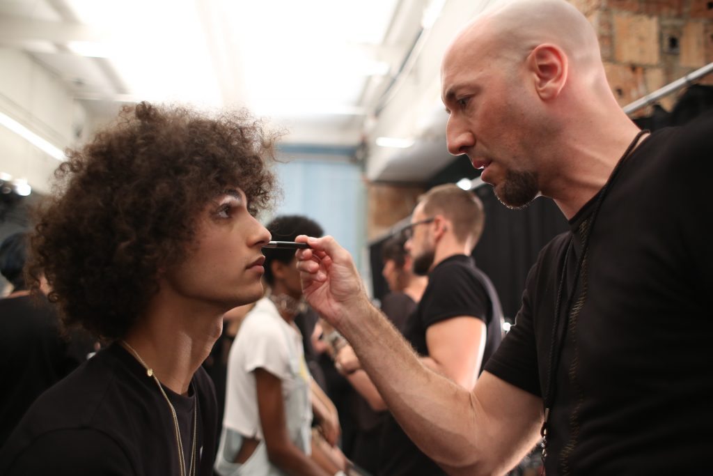 MAC Pro Makeup Artist Victor Cembellin touching up a models foundation backstage. Photo by: Tori Repp