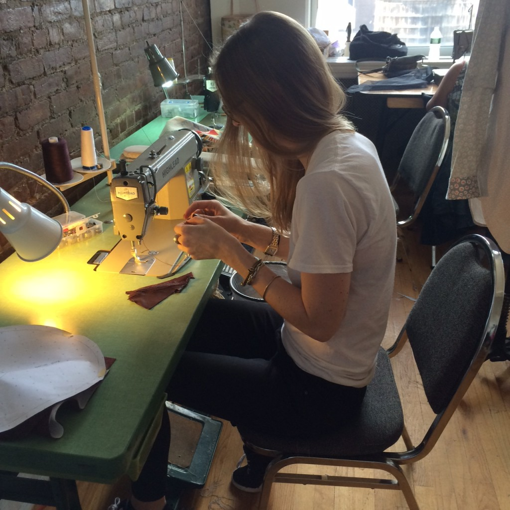 Madison Detro, MFA Fashion Design, at a sewing machine in the workroom