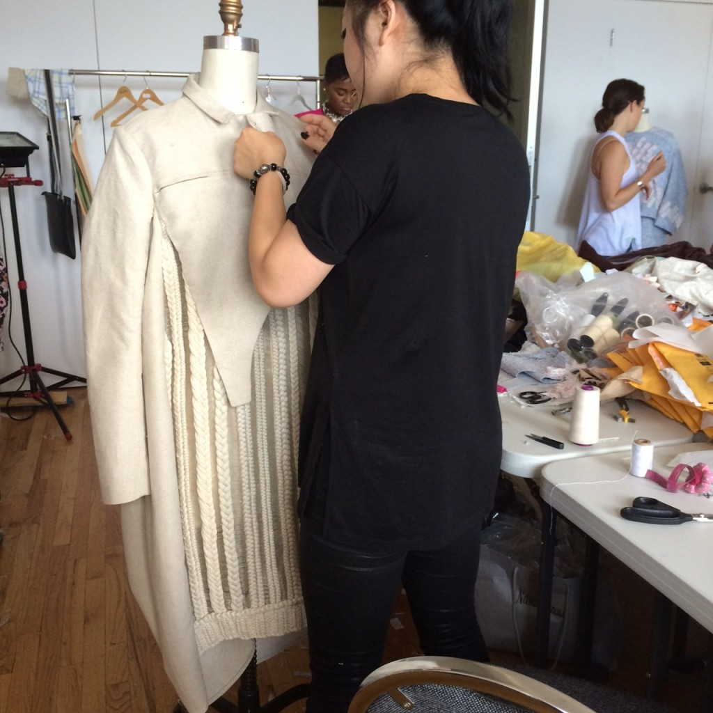 Mia Jianxia Ji, MFA Fashion and Knitwear Design, puts finishing touches on a coat.